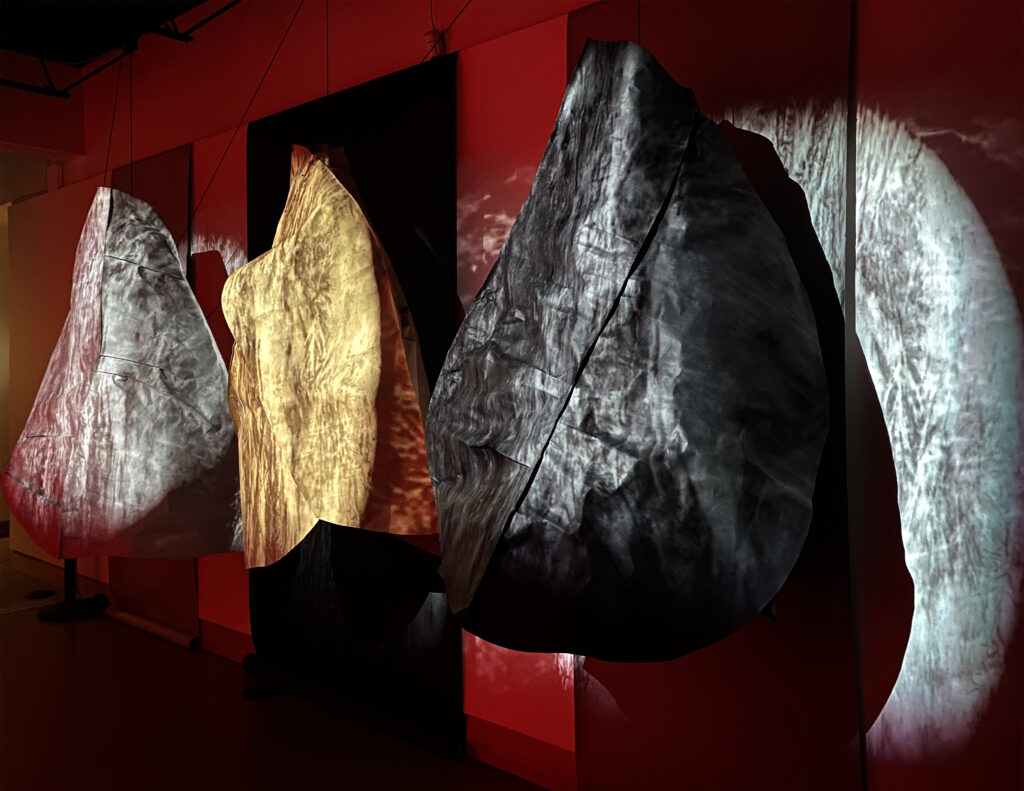 Gold and gray hanging sculptures in red light.