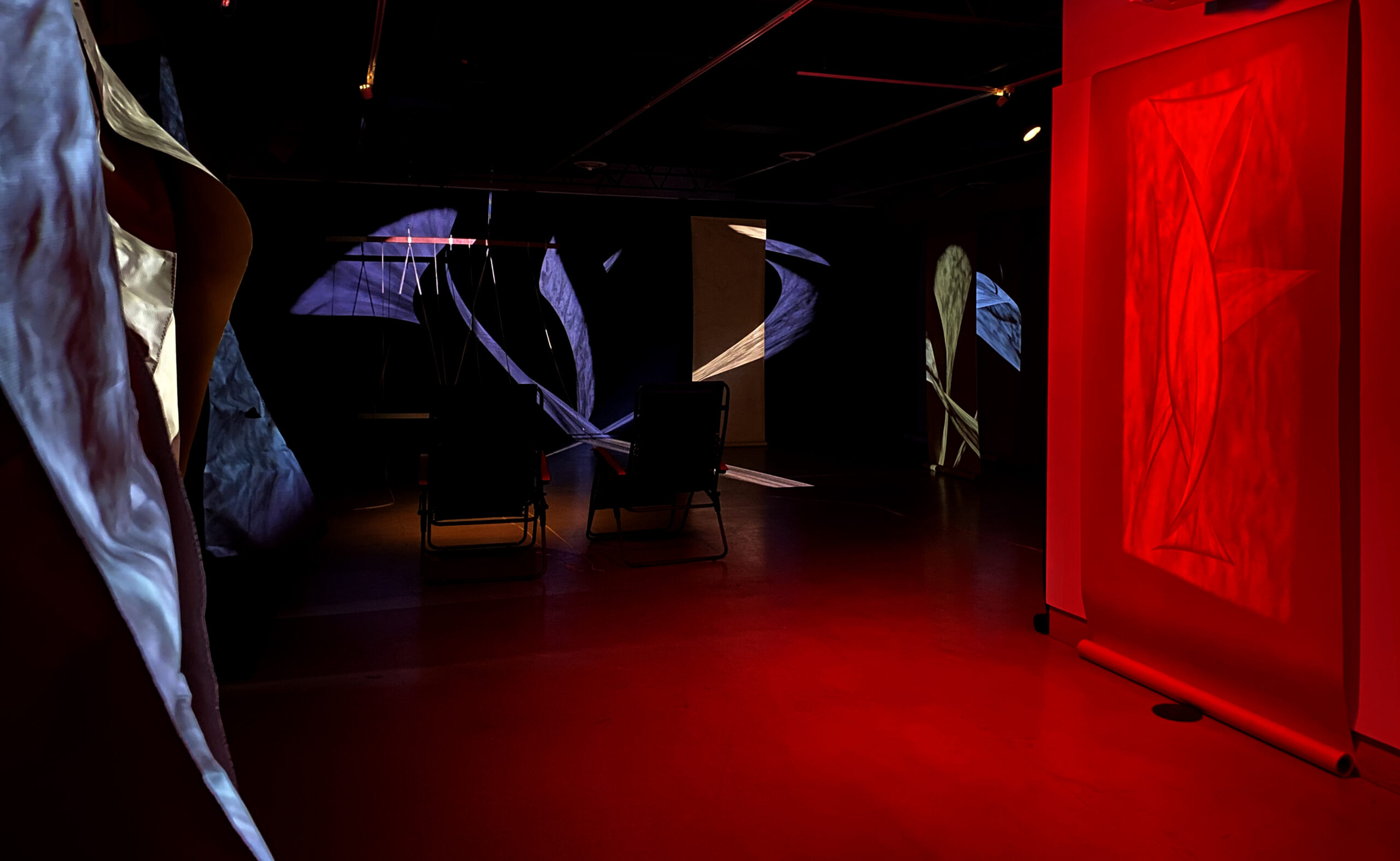 Dark room with projected pattern of purple and gold light, wash of red light on floor and wall, and two chairs in shadow.