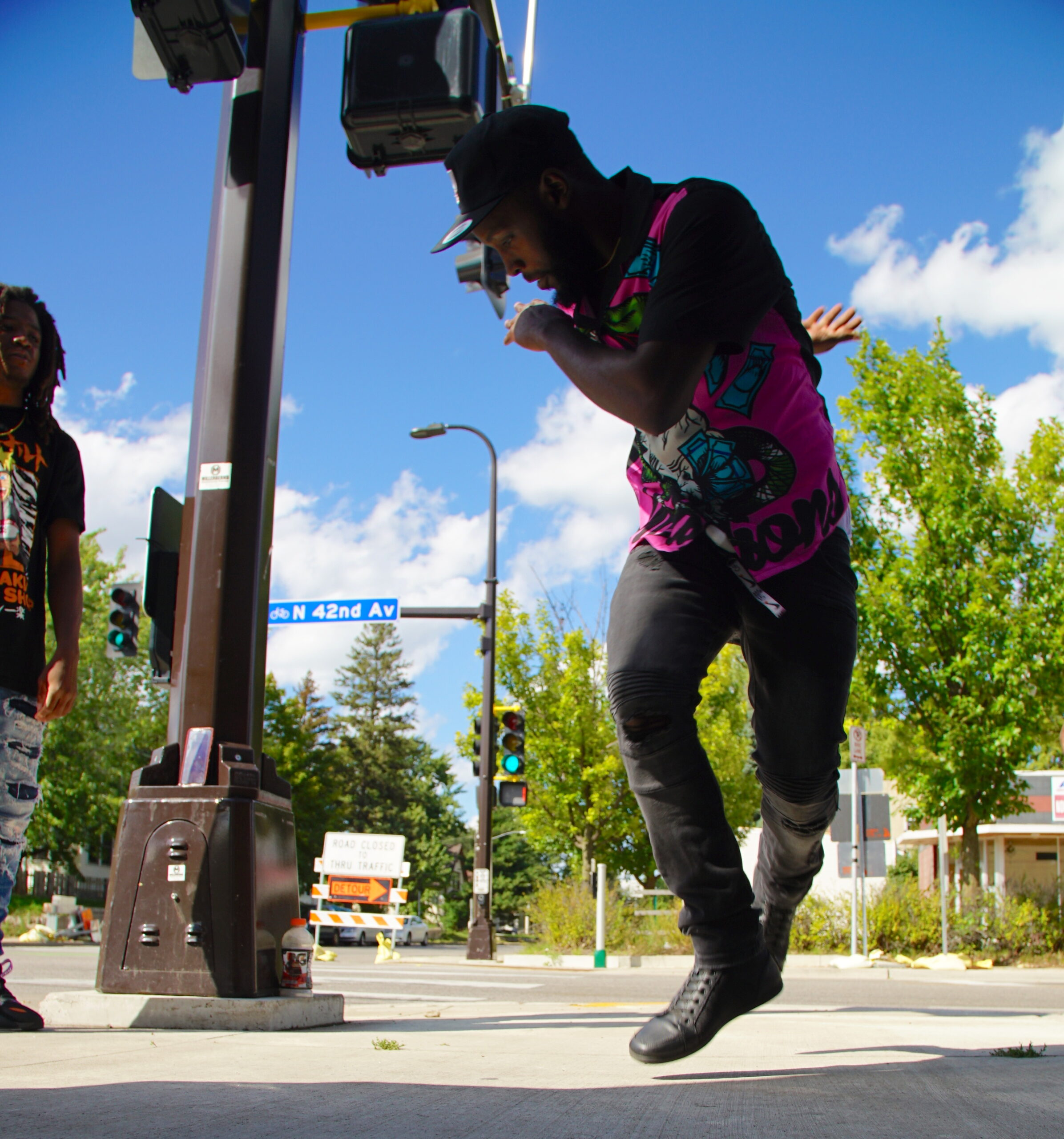 Person dancing on sidewalk, jumping and twisting over their right shoulder, with street signs, trees, and blue sky in background.