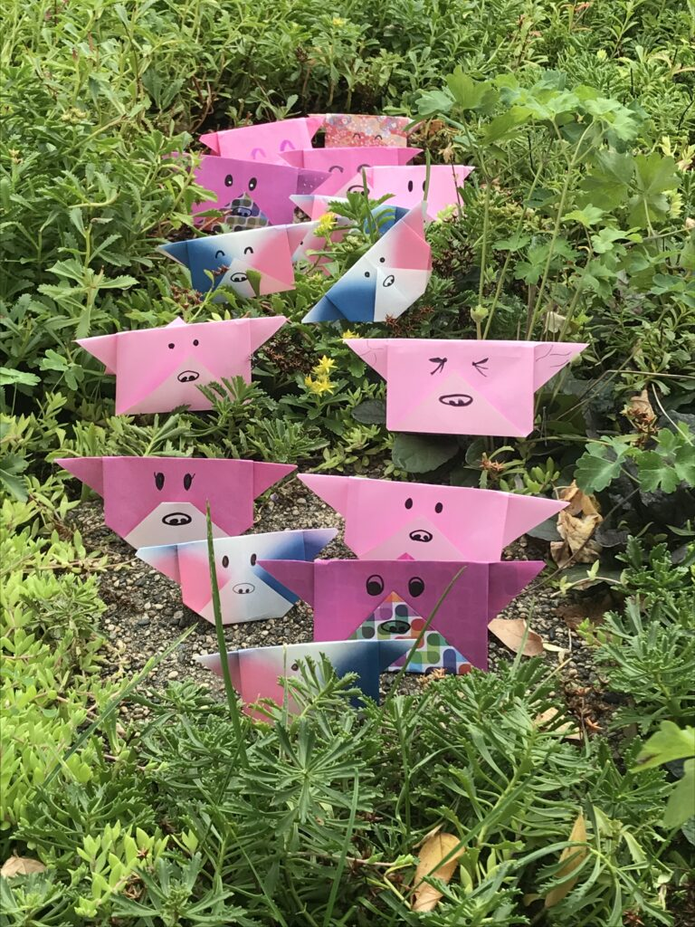 Many pink origami figures with faces drawn in black ink, arranged in green plants.