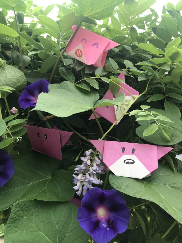 Many pink origami figures with faces drawn in black ink, arranged in green plants with purple flowers.
